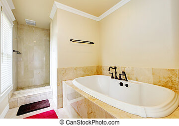 Nice empty bathroom with large white tub and shower.