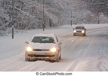 Two Cars Driving in Snow - Two cars with headlights on...