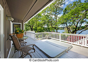 Large long balcony home exterior with hot tub and chairs, lake view.