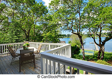 Large balcony home exterior with table and chairs, lake...