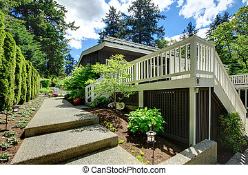 Large house back yard with large deck and walkway.