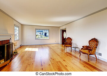 Large empty old living room interior with fireplace.
