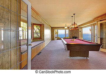 Large old room with pool table, window bench and water view.