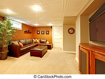 Tv media basement living room with leather sofa.