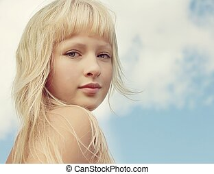 Closeup portrait of young beautiful girl on clouds sky