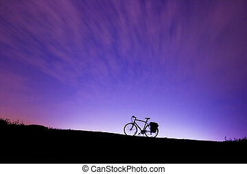 Silhouette of a bicycle on a hill
