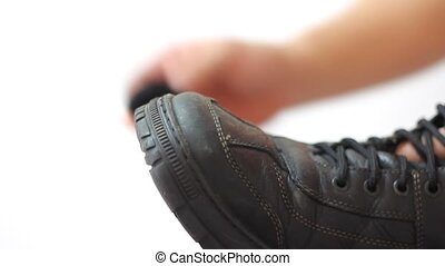 Man polishing leather black shoes on white background