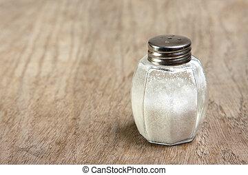 Salt shaker on wooden table - Salt shaker on brown wooden...