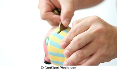 hand is putting money into piggy bank on white background