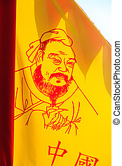 Flag with confucius painting backlit by the sun