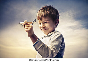 childhood - little boy with toy airplane in hand