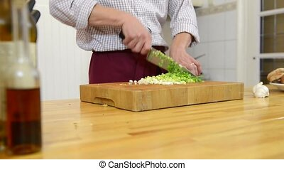 Cutting onions - Zooming in on a mans hands, cutting spring...