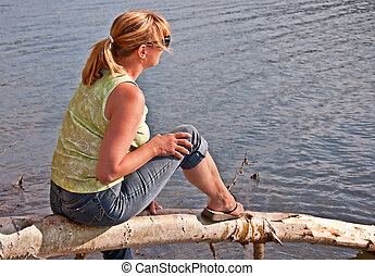 Middle Aged Woman Relaxing at Lake - This middle aged...