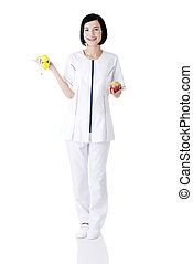Dietician - Woman dietician holding apple and dumbbells with...