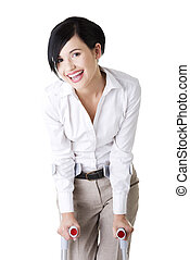 Happy young businesswoman with crutches, isolated on white....