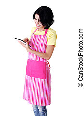 Young woman in pink apron using tablet computer, isolated