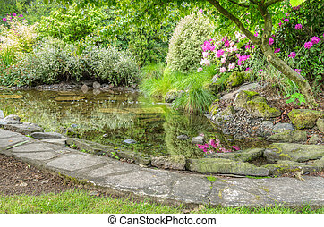 Landscaped garden scene with stone edged pond