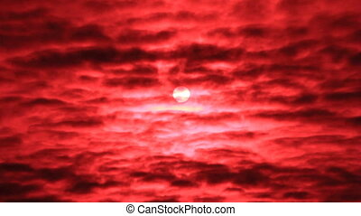 Sun behind red clouds