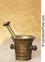 Bronze mortar and pestle on yellow blurry background