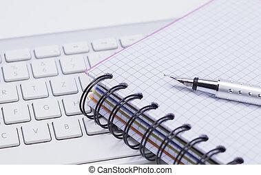 Notizbuch, Stift und Tastatur - Das Foto zeigt ein...