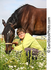Smiling teenager boy with horses at the field - Smiling...