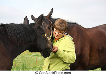 Teenager boy and horses from the herd - Teenager boy playing...