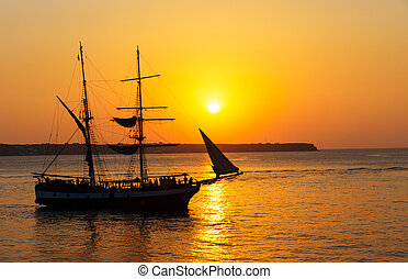 Sunset with sailing ship - A sailer sailing into a beautiful...