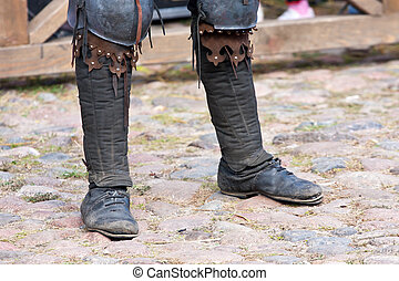 Legs of a man in the boots of a dark ages - Legs of a man in...