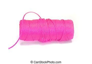 Pink sewing thread wound on a spool