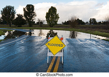 Flooded warning sign on an impassable road, San Martin,...