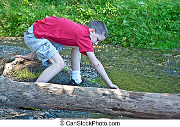 Pre-teen Boy Playing Outside Near Creek - This pre-teen...