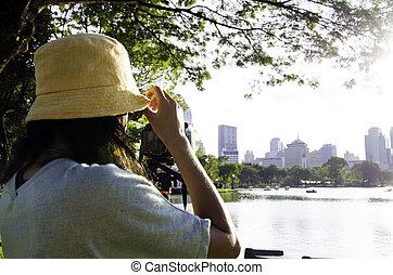 Girl taking photos by professional digital camera in lumpini...