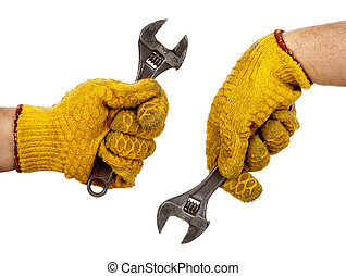 Adjustable wrench in hands with glove - Two hands with...