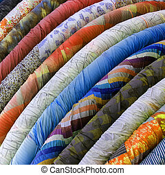 Rolls of colourful material or fabric - Stack of Rolls of...
