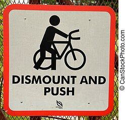 Dismount bike sign at public park - A national parks sign to...