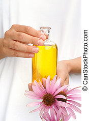 Hands of young woman holding essential oil and fresh...