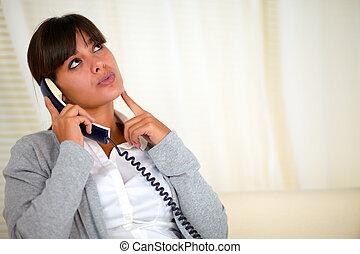 Pensive woman looking up speaking on phone