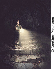 Woman holding a glowing Bible in the forest