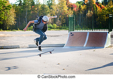 teen boy skateboarding at the local skate park on a...