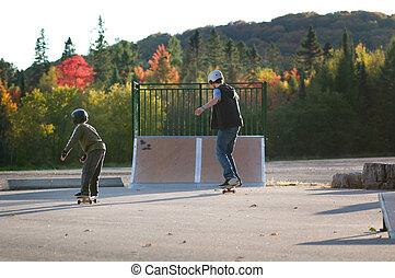 teen boy teaching younger brother to skateboard at the local outdoor skate park on a beautiful fall evening