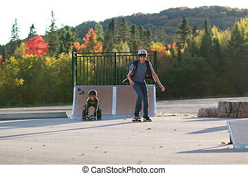 teen boy teaching younger brother to skateboard at the local...