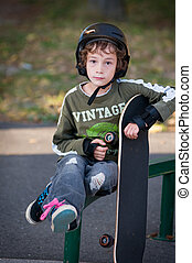 young boy wearing safty equipment learning to skateboard at a local outdoor sake park on a beautiful fall evening