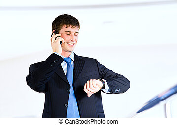 time is money - Businessman talking on cell phone and...