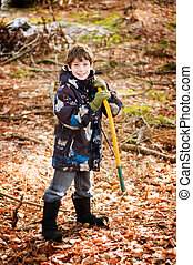 young boy with a saw to help cut down a christmas tree