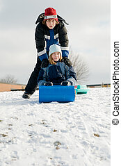 two kids sledding in winter