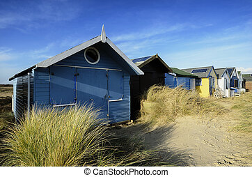 Brightly Coloured Beach Huts - Beach huts in sand dunes at...