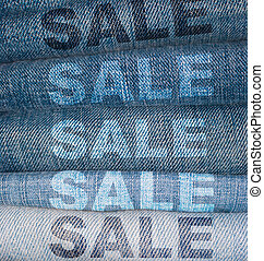 Jeans Sale - Sale Signs on Stack of Blue Jeans
