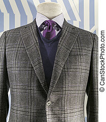 Close up of a grey checkered jacket with blue v-neck sweater...