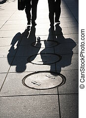 shadows of two men on the sidewalk in a big city