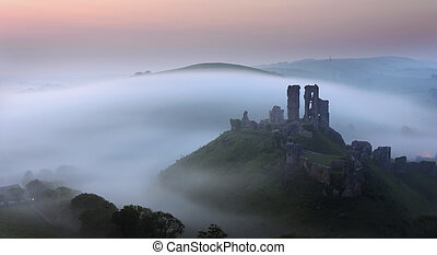 Corfe Castle - The ruins of Corfe Castle in Dorset rise out...